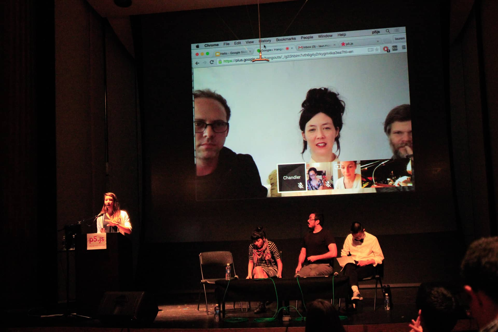 Woman speaks at a podium in an auditorium while three participants sit on the stage and another three are skyping in on the stage screen""