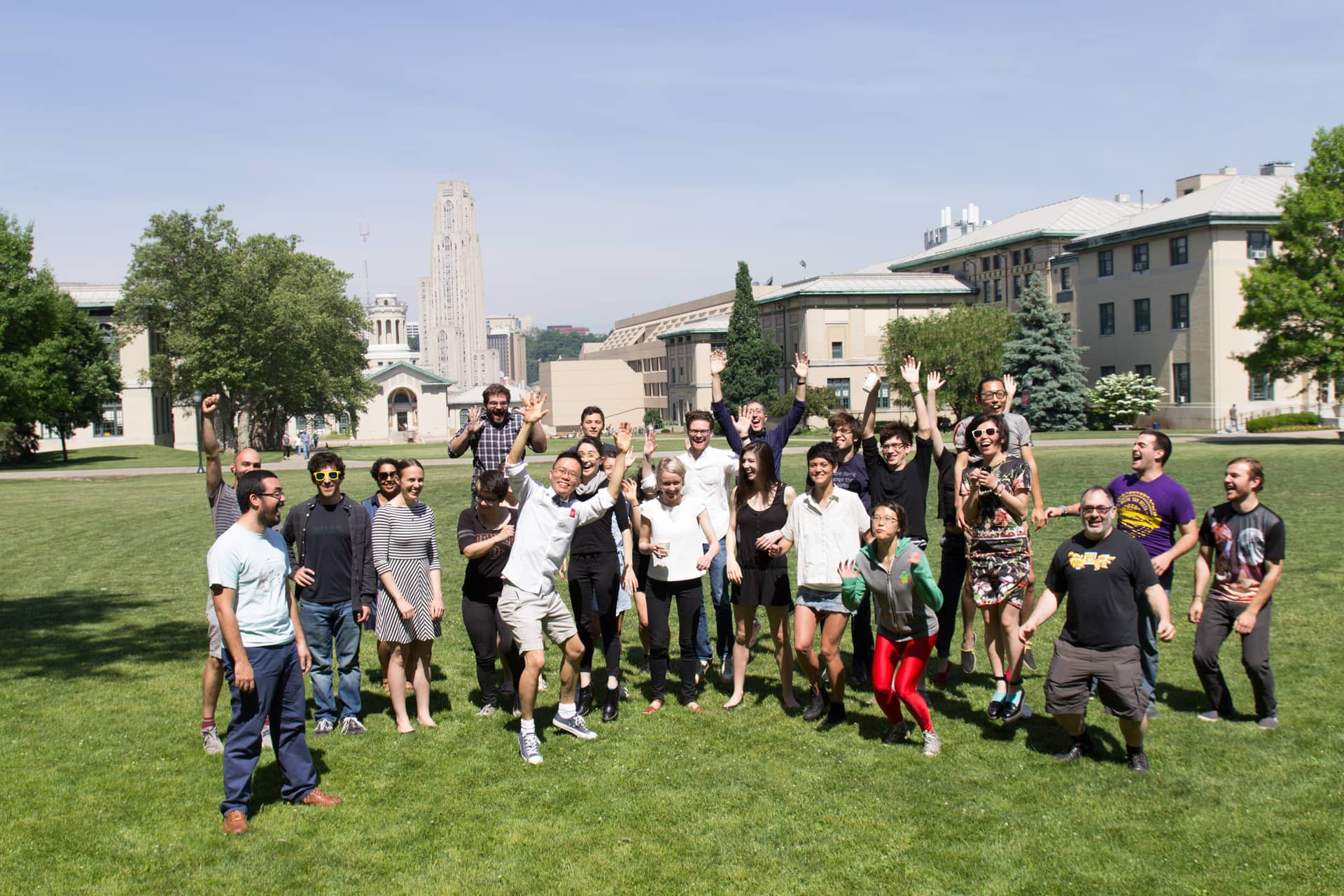 Participants jump, smile and throw their hands in the air on a green lawn""