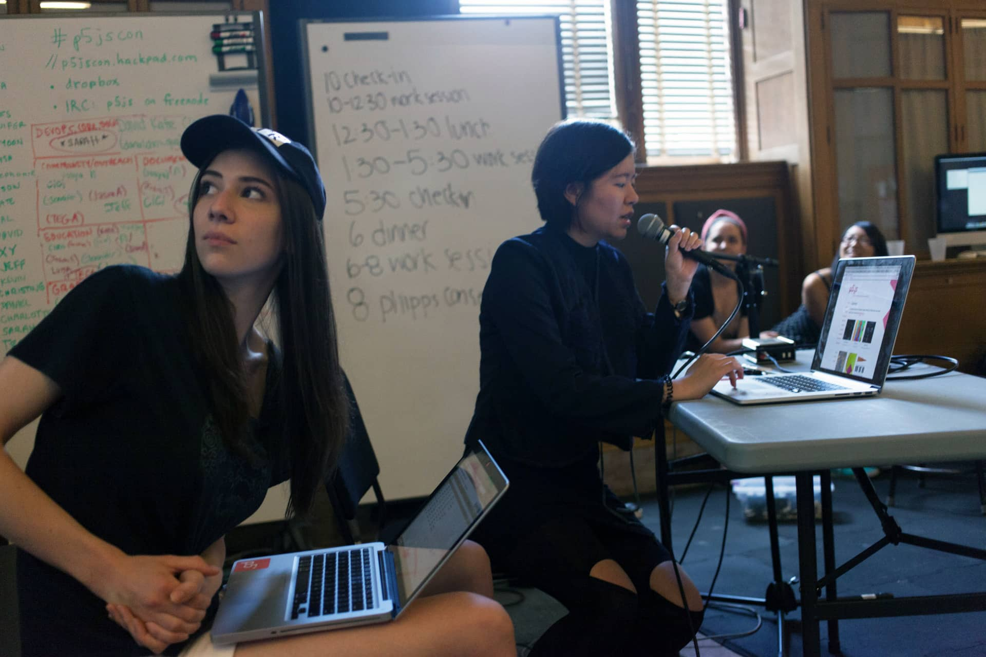 Woman reads about p5.js into a microphone to three female students""