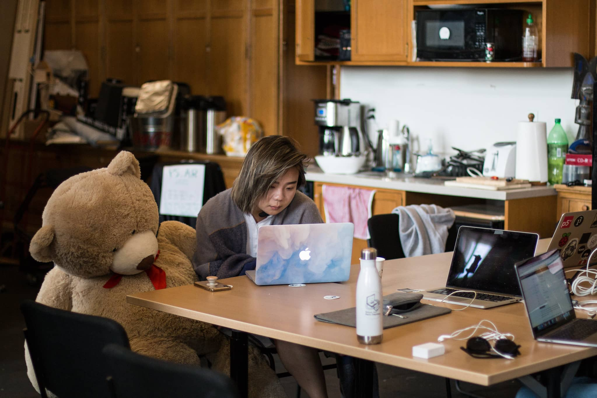 Woman sitting next to a lifesize teddy bear works on her laptop""