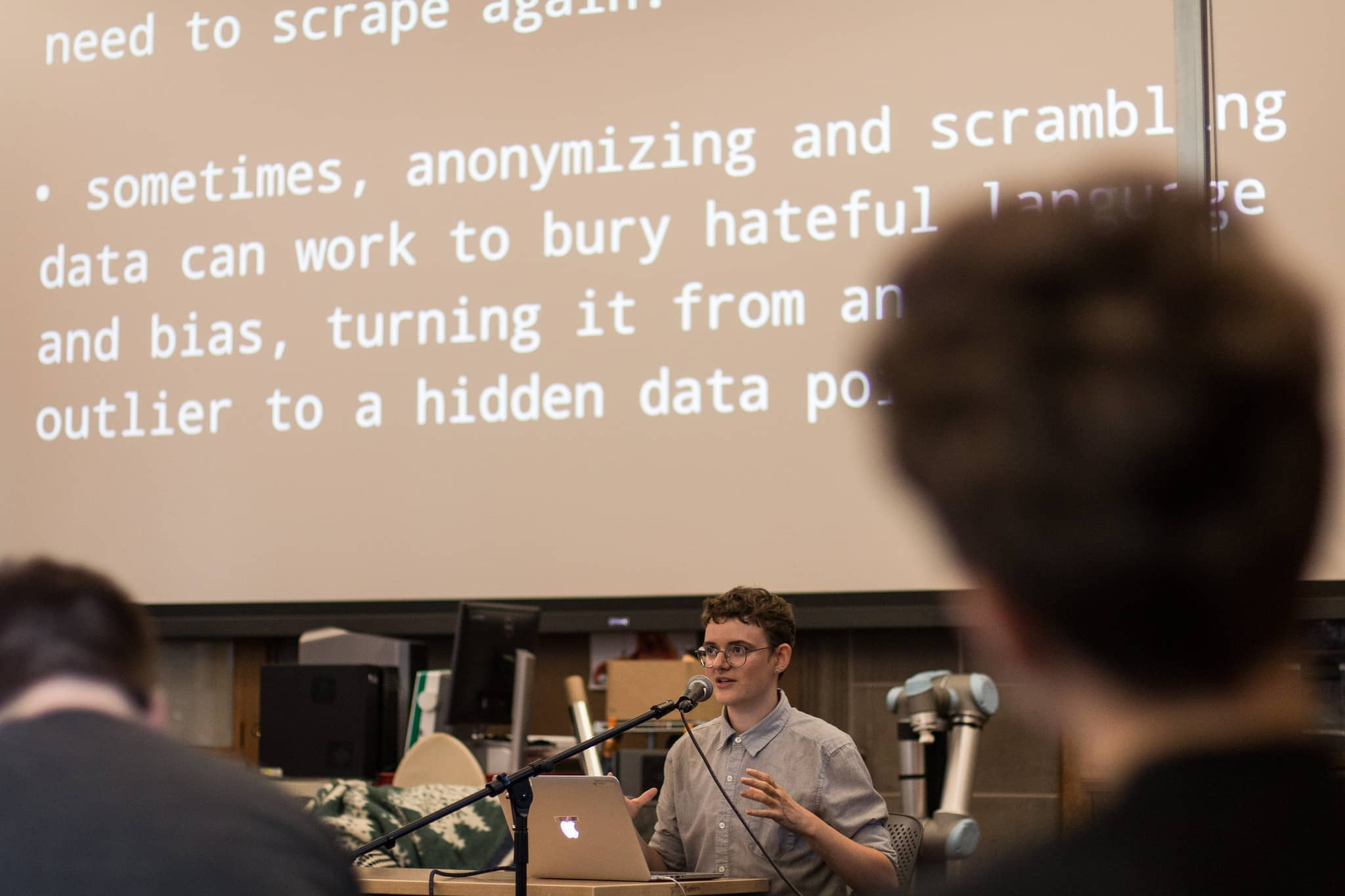 Participant speaks at a podium in front of projected text about the problem with anonymyzing data""