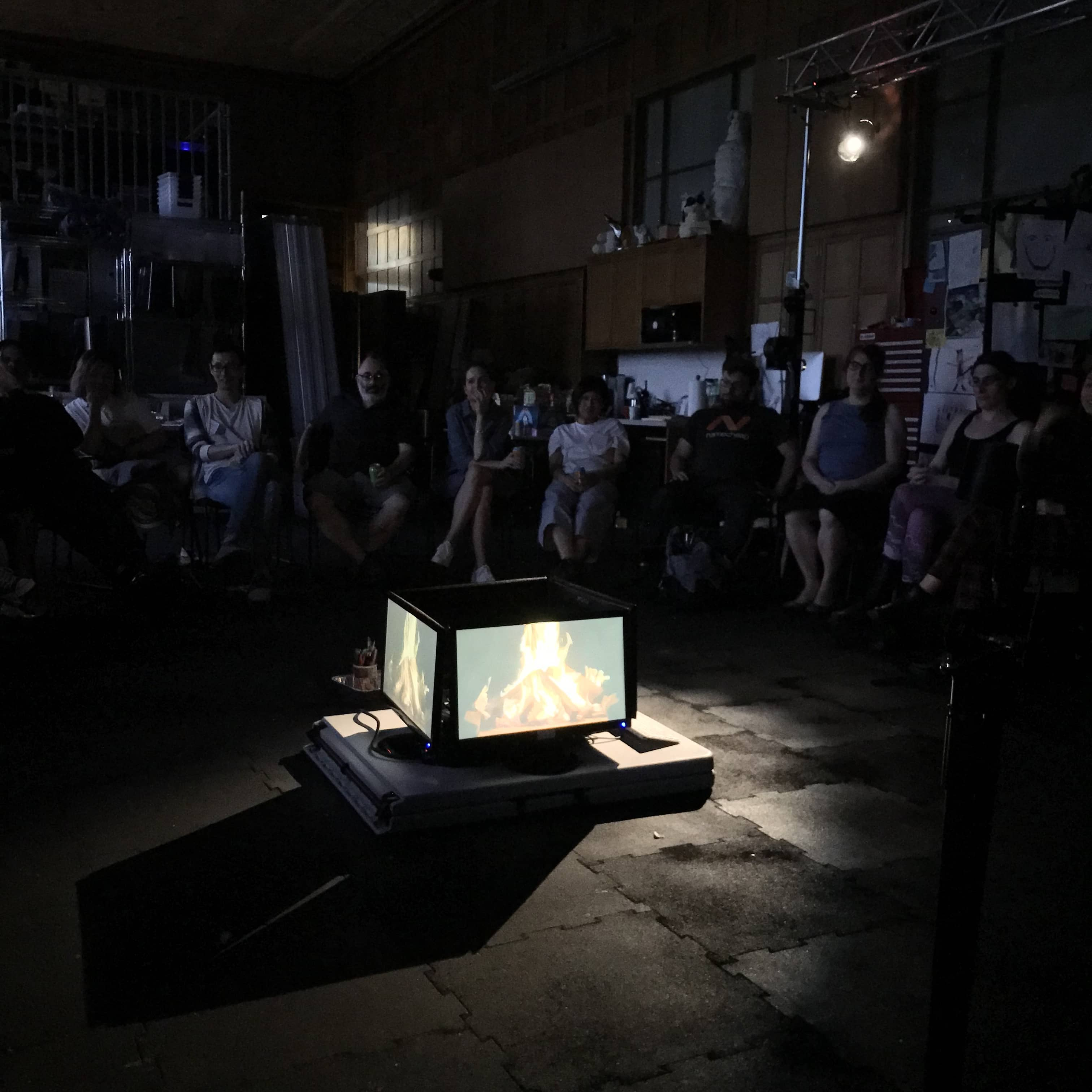 Group of people sit around campfire made from four LCD monitors.""